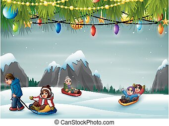 Happy children playing sledding in the snow hill