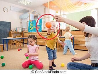 Happy children playing with ball and ring in kindergarten -...