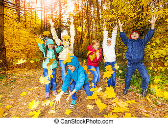 Happy children playing with flying leaves