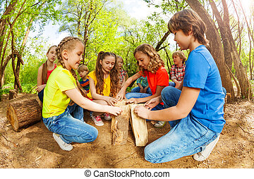 Happy children playing with logs in the forest