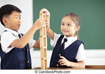 happy children playing wood blocks in classroom