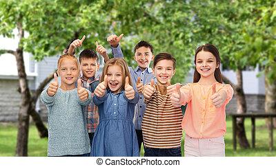 happy children showing thumbs up over backyard