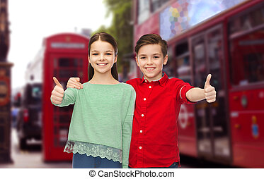 happy children showing thumbs up over london city
