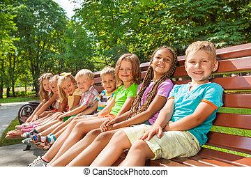 Happy children sit on the bench in park
