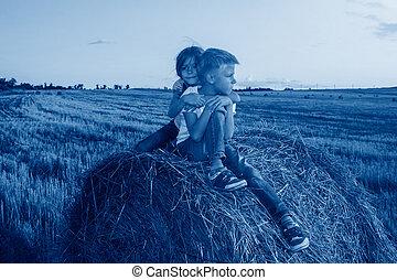 happy children sitting on haystack at sunset. girl hugged ...
