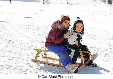 Happy children sledding on snow, mountaint park