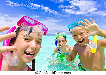 Three happy children snorkeling in tropical sea with blue sky and cloudscape background.
