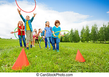 Happy children throw colorful hoops on cones while competing...