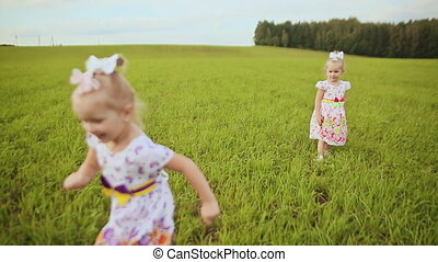 Happy children twins running around laughing and playing in the meadow in the summer.