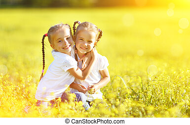 happy children twins sisters embracing in summer on nature...