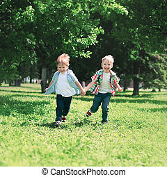 Happy children two boys brothers are running together having fun on the grass in a summer day
