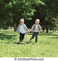 Happy children two boys brothers running together and having fun outdoors on the grass in summer day