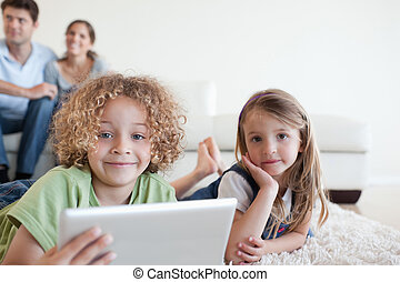 Happy children using a tablet computer while their happy parents are watching in their living room
