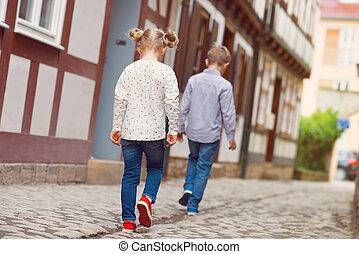 Happy children walking in sunny town