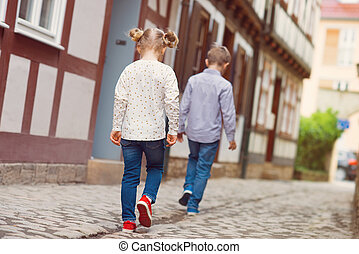 Happy children walking in sunny town