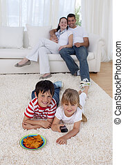 Happy children watching television on floor in living-room ...