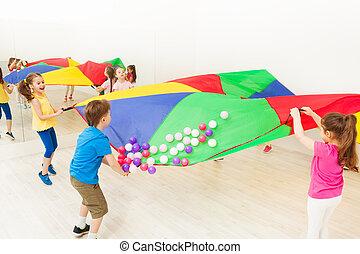 Happy children waving parachute full of balls