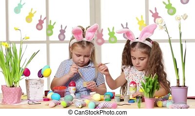 Happy children wearing bunny ears painting eggs on Easter...
