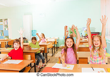 Happy large group of children with arms up sitting in classroom rows and smile in school