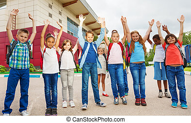 Happy children with arms up standing near school