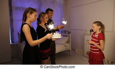 Happy children with birthday cake - Young girl is blowing...