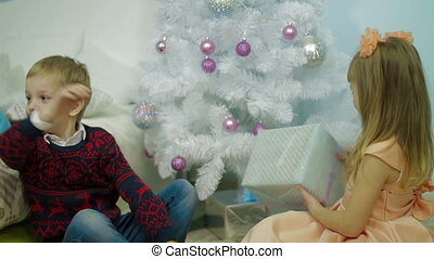 Happy Children with Christmas Gift near Christmas Tree at home