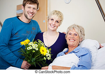 Happy Children With Flower Bouquet Visiting Mother In Hospital