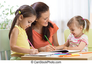 happy children with teacher drawing in classroom