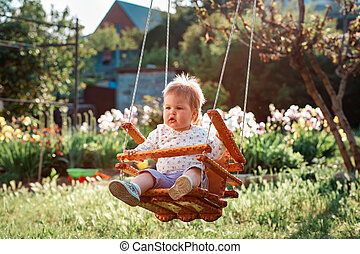 Happy Children's Day. Cute toddler with blonde hair having fun on a swing. Sunny backyard in the background. The concept of the International Children's Day