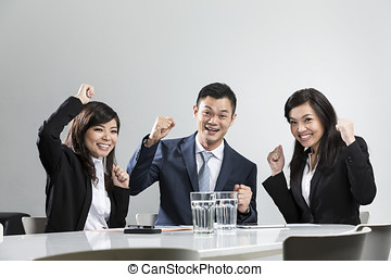 Happy Chinese business people cheering in a meeting. - Happy...