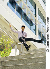 Happy Chinese Businessman Going Downstairs Sliding On Rail