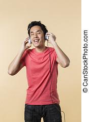 Happy Chinese man wearing earphones.