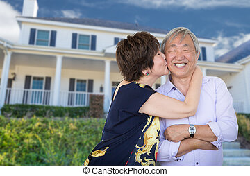 Happy Chinese Senior Adult Couple Kissing In Front Of Custom House.