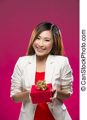 Happy Chinese woman holding a christmas gift.