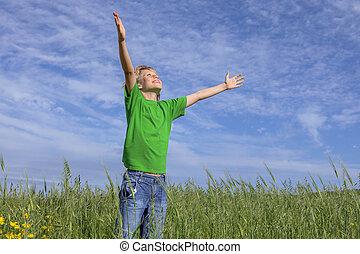 happy christian boy arms raised in prayer.