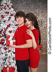 Happy Christmas couple embrace in red clothes. Young brunette girl hugging handsome man with gift box. Two teen having fun over xmas interior.