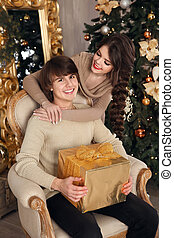 Happy Christmas couple in love. Young brunette girl hugging handsome man with gift box. Guy relax on modern armchair over xmas interior.