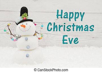 Happy Christmas Eve greeting, Some snow and a snowman on weathered wood with text Happy Christmas Eve