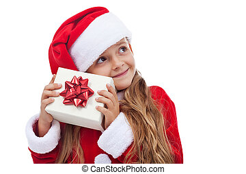 Happy christmas girl checking present - trying to figure out what is inside, isolated