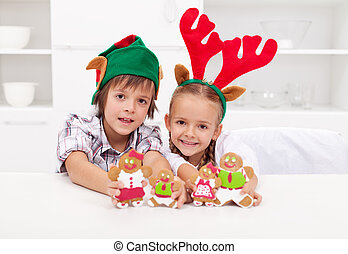 Happy christmas kids holding decorated gingerbread people