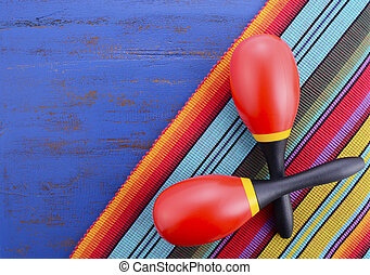 Happy Cinco de Mayo background with colorful maracas on Mexican theme dark blue distressed table with copy space.