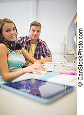 Happy classmates doing assignment together in the computer room