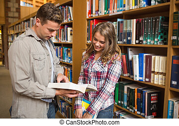 Happy classmates standing in library