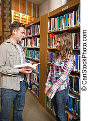 Happy classmates standing in library talking