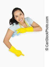 Happy cleaning lady pointing to white surface - Happy ...