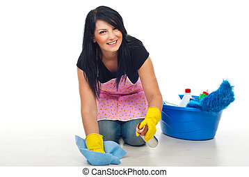 Happy cleaning woman kneel and floor wipe with a dust cloth...