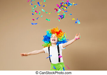Happy clown boy with large colorful wig. Let's party! Funny kid clown. 1 April Fool's day concept. Portrait of a child throws up a multi-colored tinsel and confetti.