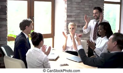 Happy colleagues applaude at the end of a business meeting -...