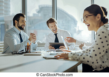 Happy colleagues laughing at funny joke during meeting