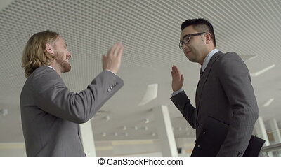 Happy Colleagues - Low angle of two men giving high-five